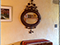 Photo of an oval antique mirror hanging on the bedroom wall